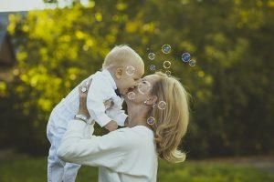 母親が赤ちゃんを笑顔で抱きあげている