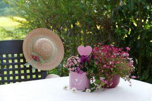 庭にあるテーブルの上に花と麦わら帽子